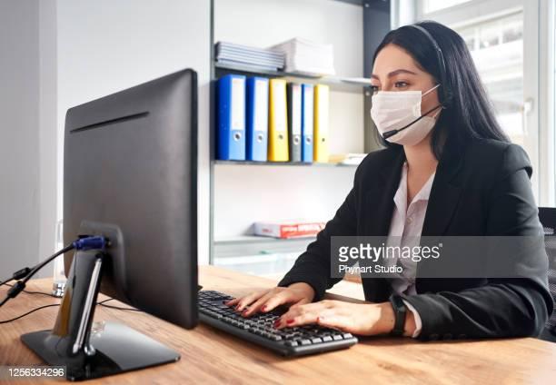 operador de telemarketing trabalhando evitando covid-19 no escritório - attending - fotografias e filmes do acervo