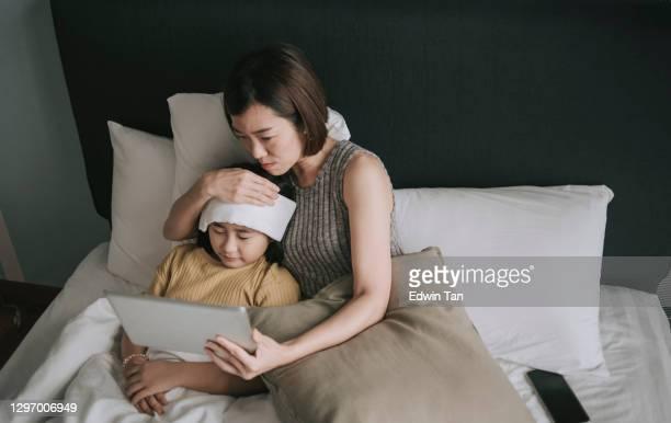 telemedizin telemedizin asiatische chinesische besorgt eiserne mutter mit digitalen tablette kommunizieren mit arzt kinderarzt auf ihre tochter krankheit - mother daughter webcam stock-fotos und bilder