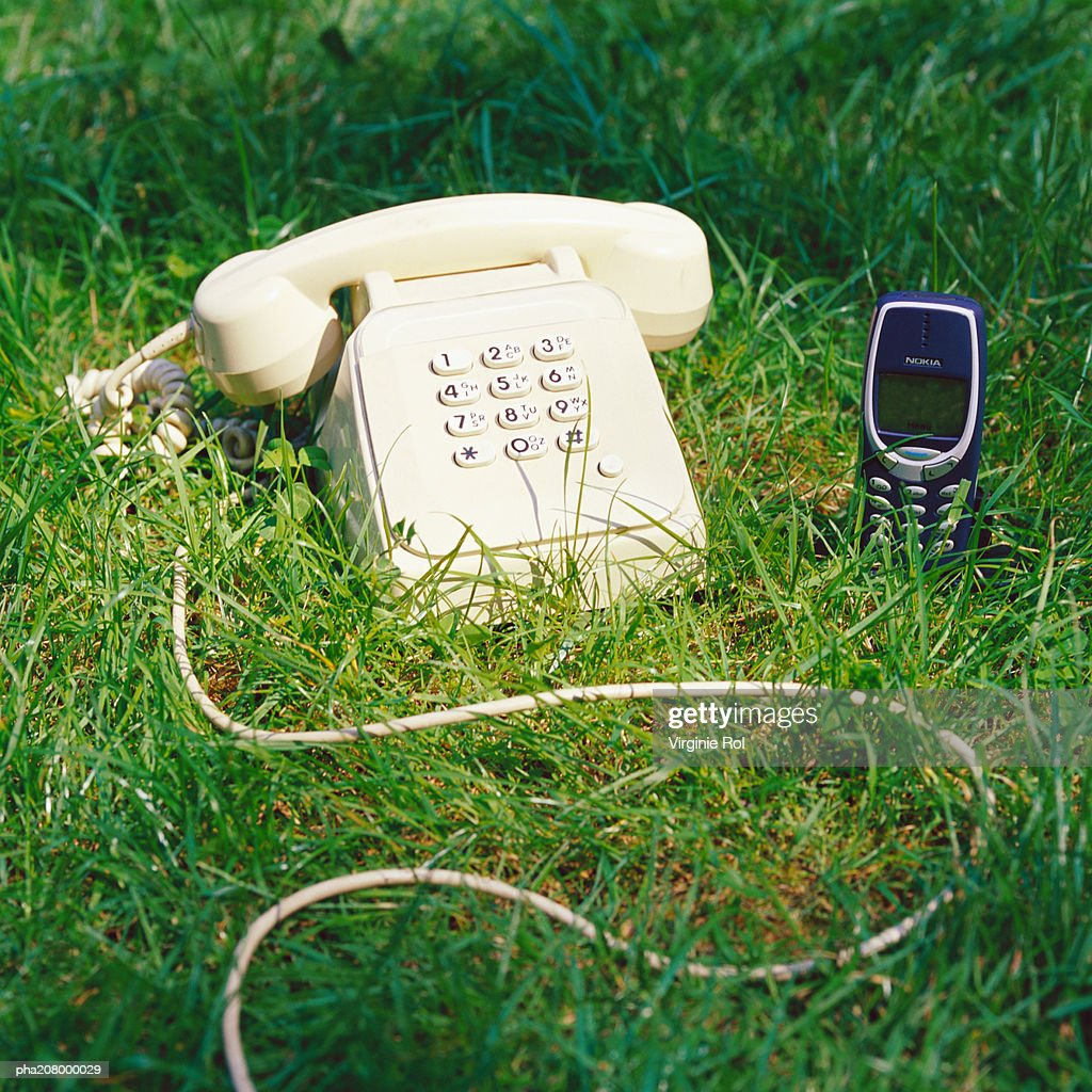 Telephone and cell phone on grass. : Stockfoto