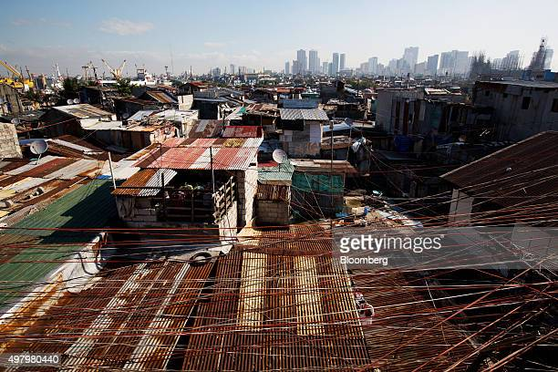 Telephone and electricity wires hang above slum housing in the Tondo district of Manila the Philippines on Thursday Nov 19 2015 Philippine gross...