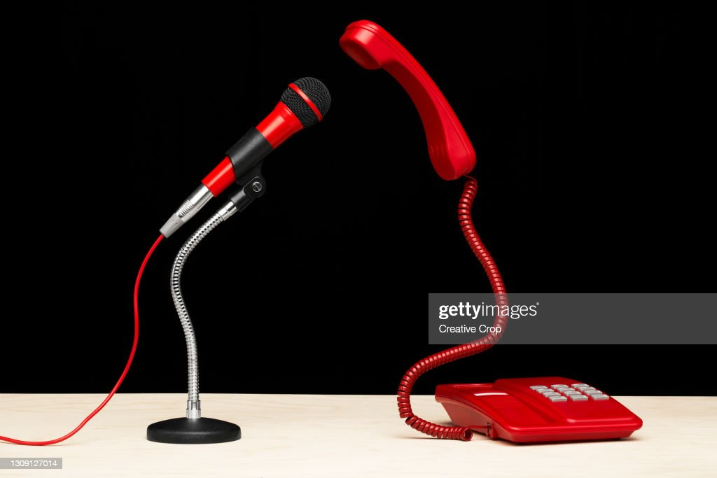 A telephone and microphone facing each on a desktop : Stock Photo