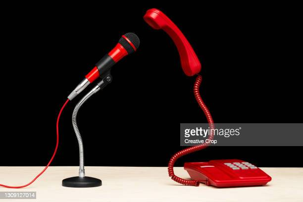 a telephone and microphone facing each on a desktop - microzoa stock pictures, royalty-free photos & images