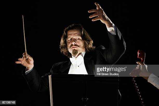 Telephone being handed to orchestral conductor