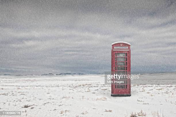 Telephone booth in snowy landscape