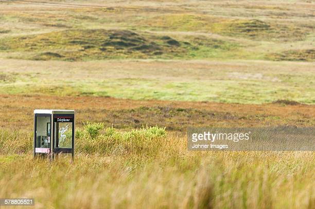Telephone booth on meadow