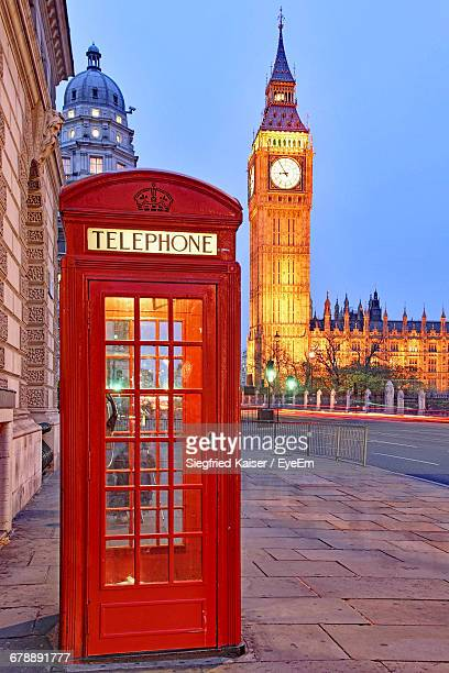 telephone booth on sidewalk against illuminated big ben - telephone booth stock pictures, royalty-free photos & images