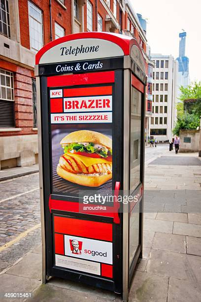 telephone booth with fast food advertising, london - telephone box stock pictures, royalty-free photos & images