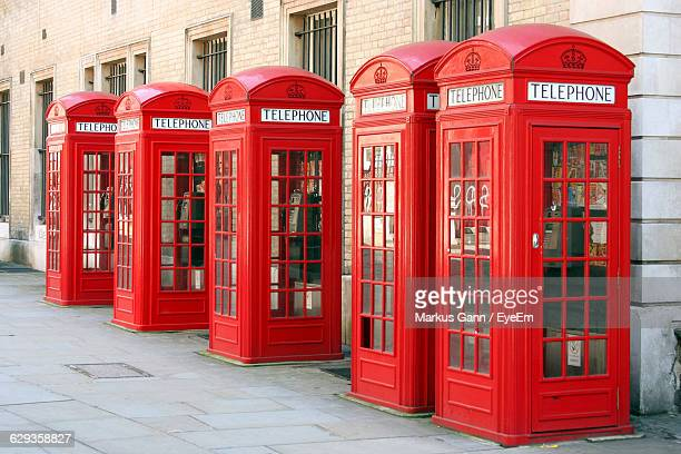telephone booths on sidewalk against building - telephone box stock pictures, royalty-free photos & images