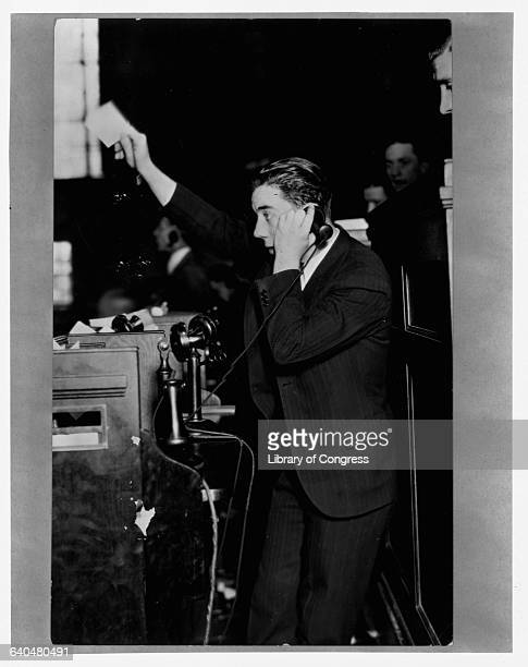 A telephone clerk at the New York Stock Exchange calling one of the members on the floor