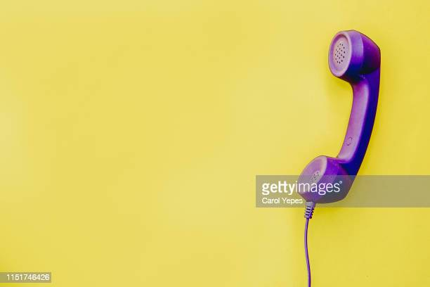 telephone handset in  yellow background - telefonist stock-fotos und bilder