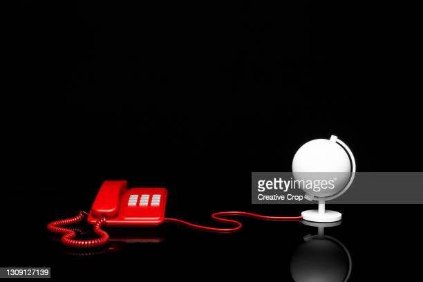 a telephone is connected to a desk globe via a cable - microzoa stock pictures, royalty-free photos & images