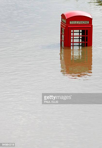 A telephone kiosk is seen in flood waters in the Catcliffe area of Sheffield 26 June 2007 as the level of river water continued to rise across South...