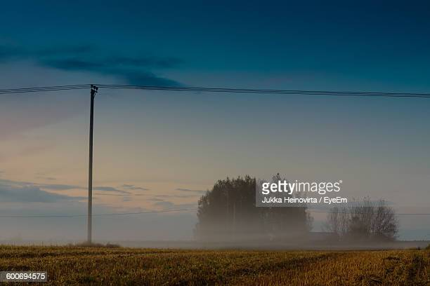 telephone pole on field against sky - heinovirta stock pictures, royalty-free photos & images
