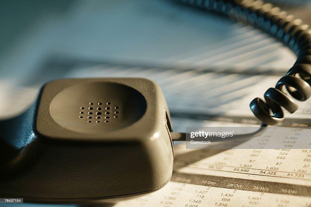 Telephone receiver atop newspaper : Stockfoto