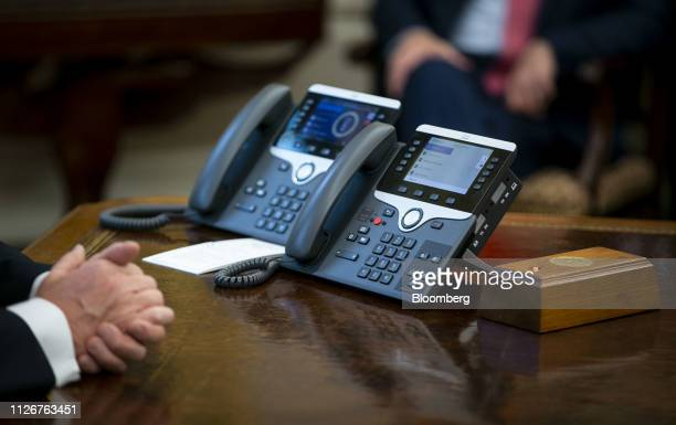 Telephone sits on the Resolute Desk as U.S. President Donald Trump speaks during a trade meeting with Liu He, China's vice premier and director of...