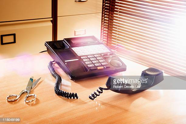 telephone with severed cord next to scissors. - newpremiumuk stock pictures, royalty-free photos & images