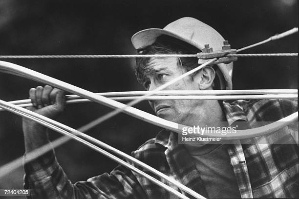 Telephone worker installing cable TV lines.