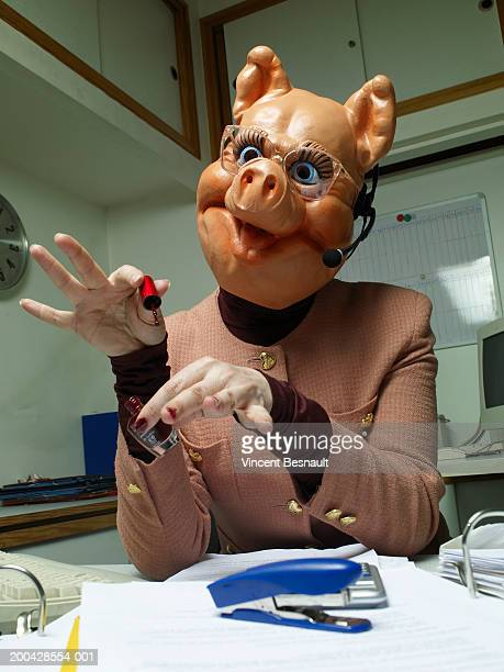telephonist wearing plastic pig mask painting fingernails at desk - funny customer service stock pictures, royalty-free photos & images