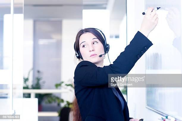 telephonist writing on whiteboard in office - sigrid gombert stock-fotos und bilder