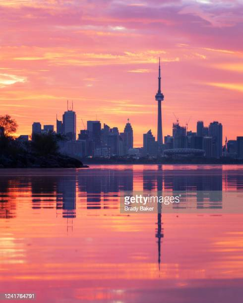 telephoto view of toronto city skyline reflected in calm lake ontario with dramatic sunrise - toronto stock pictures, royalty-free photos & images