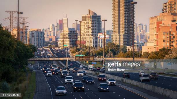 telephoto view toward downtown toronto with commuter traffic on highway - toronto stock pictures, royalty-free photos & images