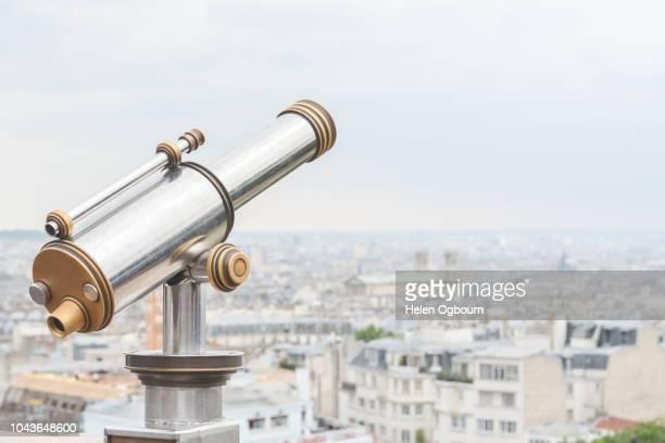telescope at montmartre looking across paris city buildings - longue vue photos et images de collection