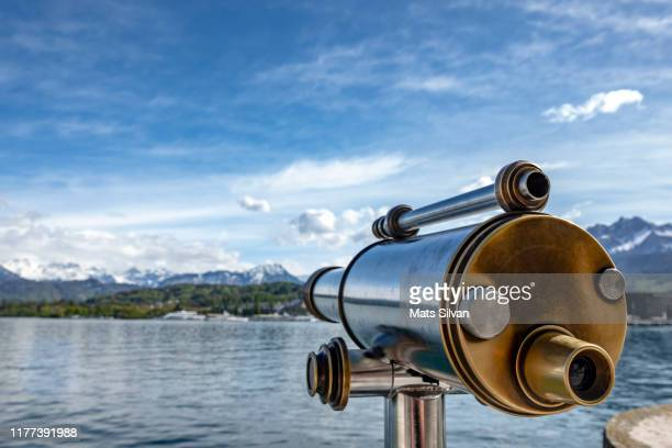 telescope over alpine lake and snow-capped mountain - zoom in stock pictures, royalty-free photos & images