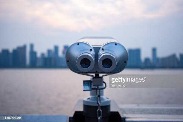 a telescopic view of a distant skyline with a telescope at the city's observatory - binoculars stock pictures, royalty-free photos & images