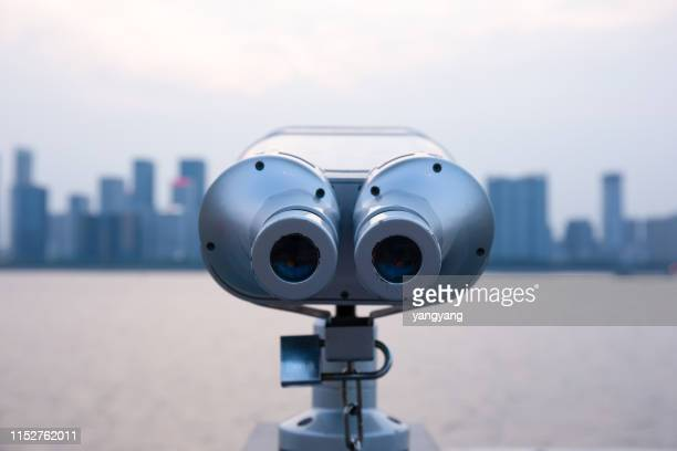 a telescopic view of a distant skyline with a telescope at the city's observatory - telescope stock pictures, royalty-free photos & images