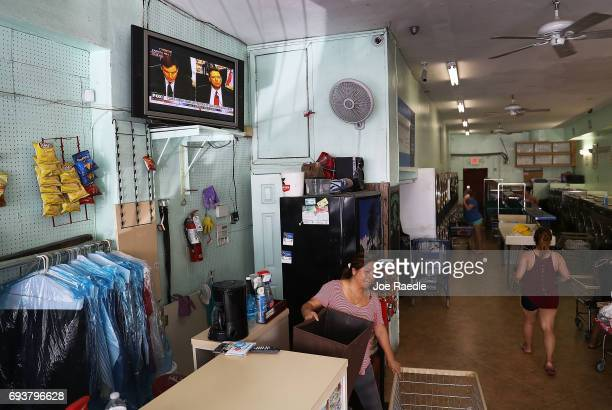 Televised broadcast of former FBI Director James Comey testifying before the Senate Intelligence Committee is seen at a laundromat on June 8, 2017 in...