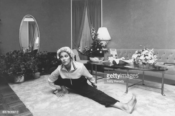 Television actress Lynda Carter stretching in a living room in 1979