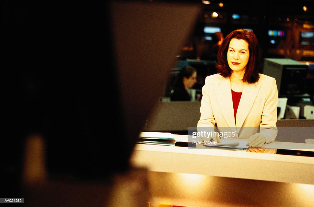 Television anchorwoman sitting at desk smiling at camera : Stock Photo