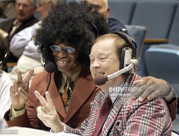 ESPN television announcers Len Elmore and Mike Patrick pose for pictures dressed in 1980s clothing before the start of a retro night game between the...
