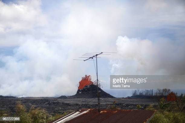 A television antenna stands at a residence as lava erupts from a Kilauea volcano fissure nearby in Leilani Estates on Hawaii's Big Island on May 24...