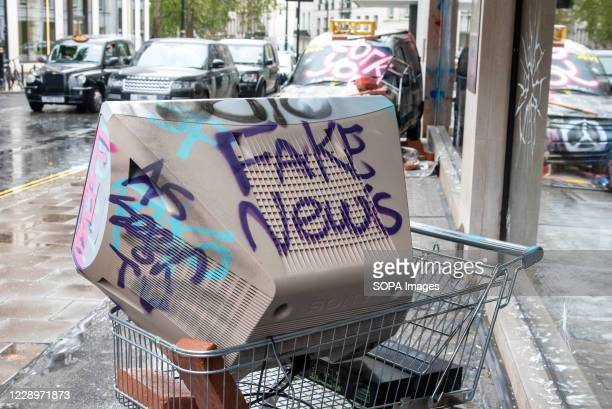 Television at a shopping trolley with the words Fake News sprayed on it, which is part of an art installation including a wrecked car with graffiti...