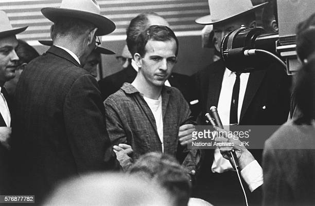 A television broadcast captures guards and secret service agents escorting Lee Harvey Oswald through the Dallas police headquarters two days after...