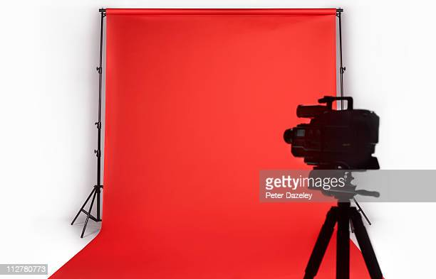 Television camera against red backdrop