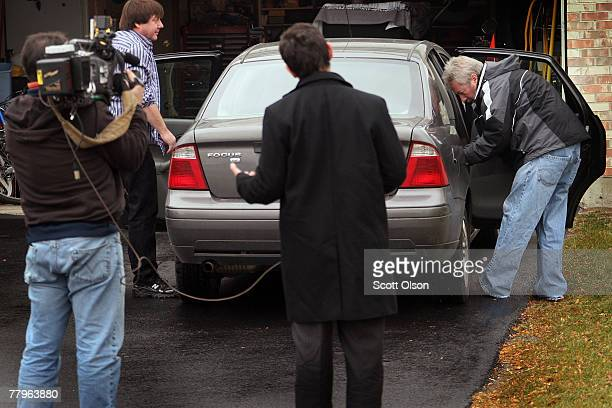 A television camera crew tapes former Bolingbrook Illinois police Sgt Drew Peterson as he straps an infant's car seat into a car in front of his home...