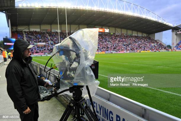 A 3D television camera is protected by the rain during the match
