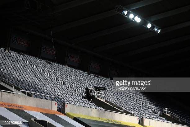 Television camera operator works amongst the empty seats, during the English Premier League football match between Newcastle United and Chelsea at St...
