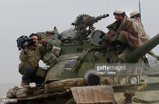 A television camera person instructs a Northern Alliance soldier while filming him on his tank tank near the frontline at Tora Bora in Afghanistan...