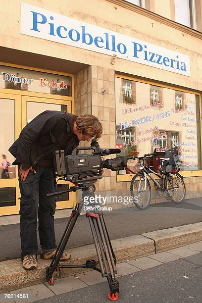 A television cameraman films in front of the Picobello Pizzeria August 22 2007 in Muegeln Germany A group of approximately 50 youths some of whom...
