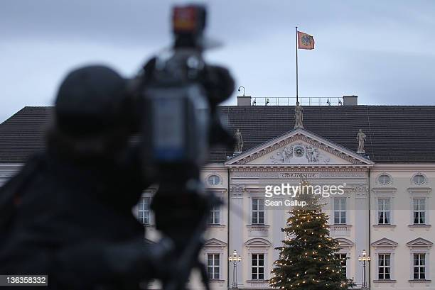 A television cameraman films Schloss Bellevue presidential palace on January 3 2012 in Berlin Germany German President Christian Wulff is coming...