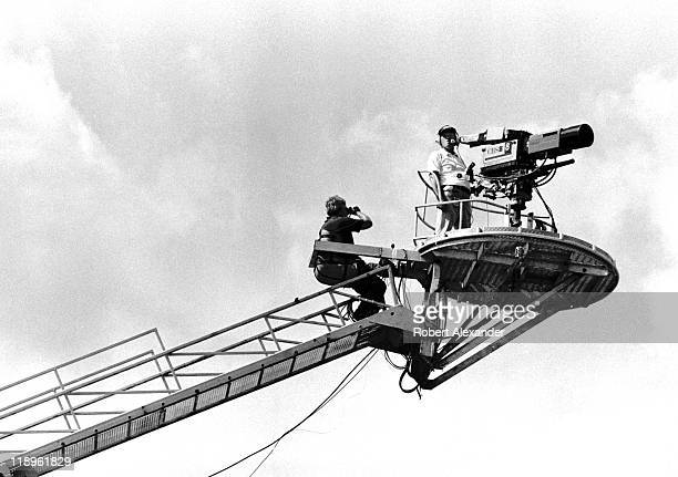 CBS television cameraman on a boom watches the action at the 1984 Daytona 500 on February 19 1984 in Daytona Beach Florida as the Goodyear Blimp...