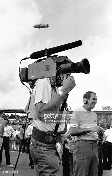 CBS television cameraman prepares to broadcast CBS announcer and former NASCAR champion Ned Jarrett as the Goodyear blimp flies overhead at the 1984...