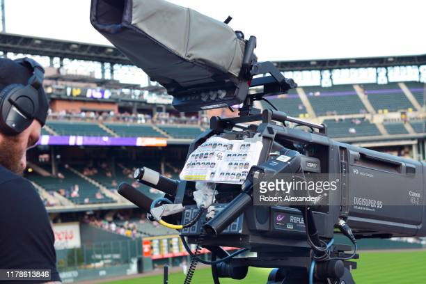 Television cameraman prepares to operate a TV camera during a live broadcast of a Colorado Rockies Major League Baseball game at Coors Field in...