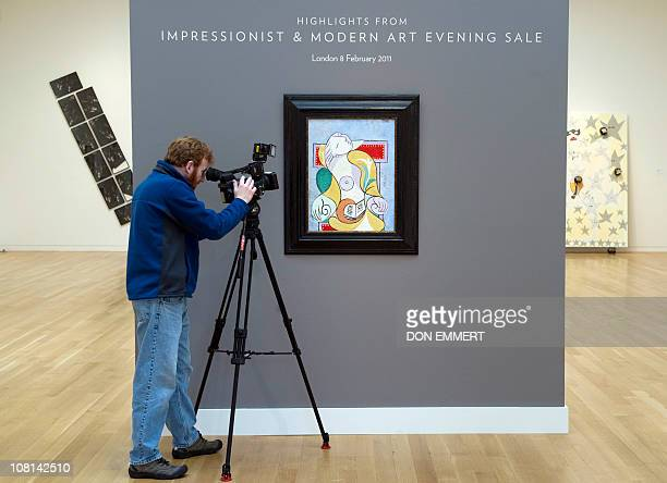 A television cameraman takes video of Pablo Picasso's La Lecture on January 11 2011 at Sotheby's in New York The painting is one of more than fifty...