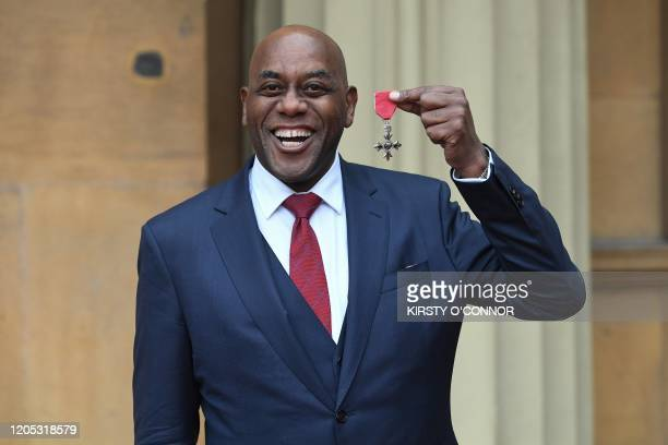 Television Chef Ainsley Harriott poses with his medal after being appointed an Officer of the Order of the British Empire for services to...