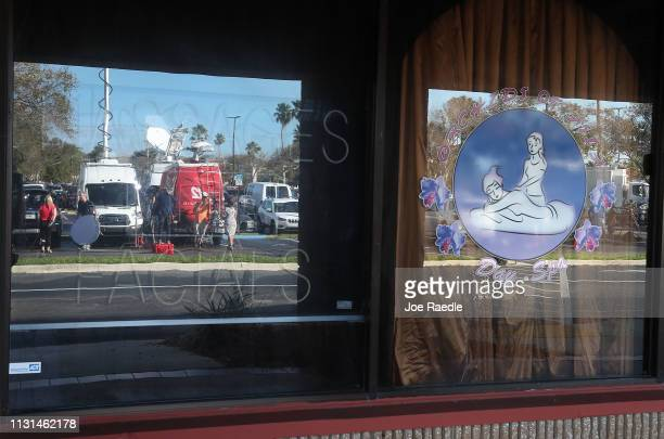 Television crews are reflected in the window of the Orchids of Asia Day Spa after New England Patriots owner Robert Kraft is charged with allegedly...