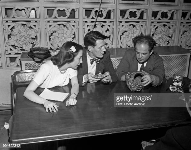 Television director Frances Buss emcee and producer Gil Fates and art appraiser Sigmund Rothschild examine items on the CBS television program...